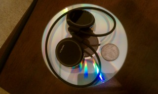 The Nuvelli headset sitting on a Compact Disc with a USA 2007 Wyoming Quarter